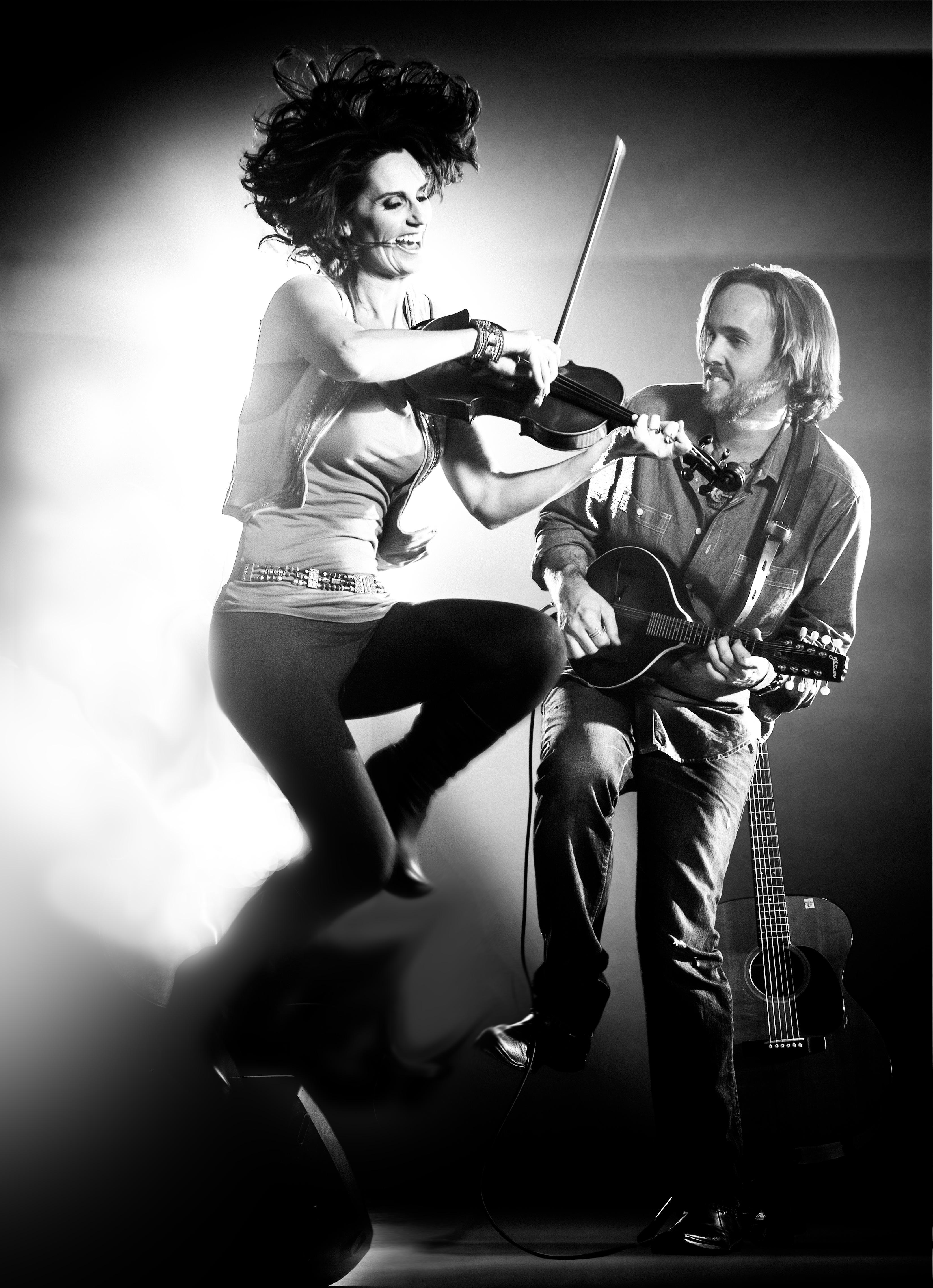 Woman plays fiddle, man plays guitar.