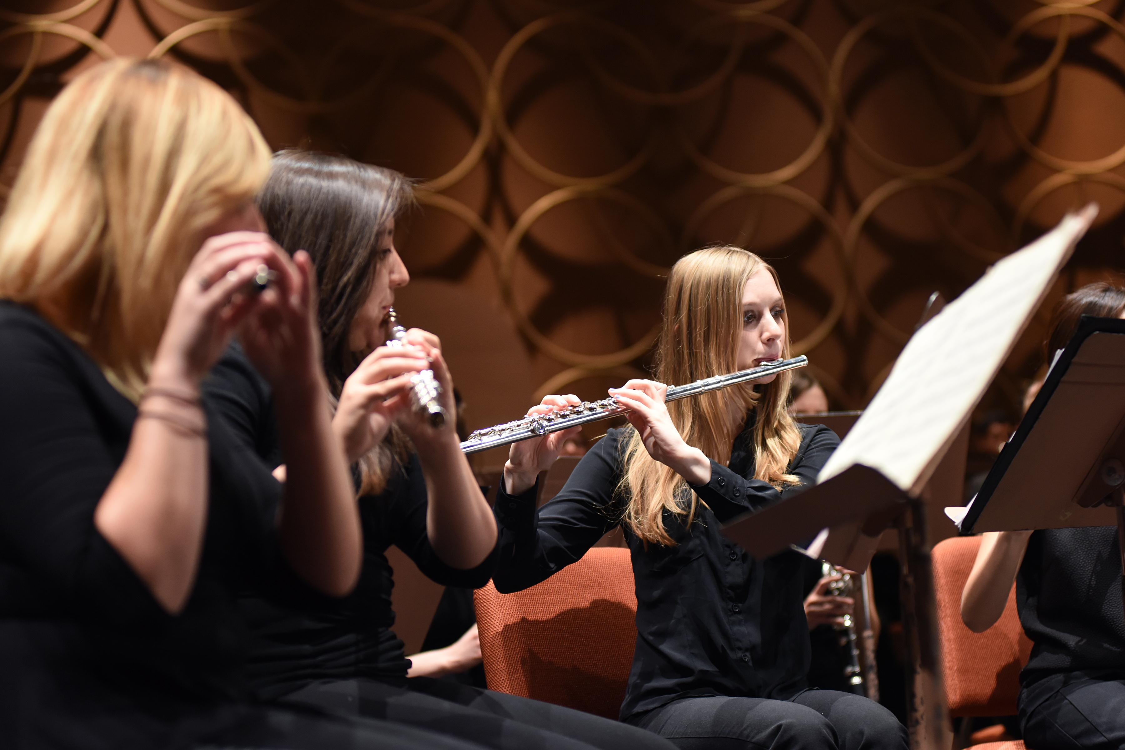 Women play flutes on stage.